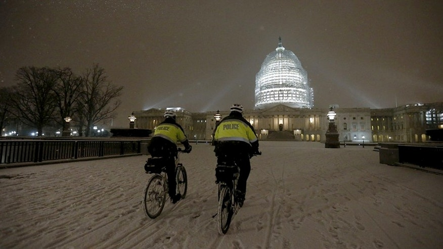 Police patrol on their bikes in Washington, D.C. on Wednesday evening as snow fell.  Some predict as much as two feet of snow in Washington, D.C. --and that's on top of covering that hit the Capitol Wednesday evening.