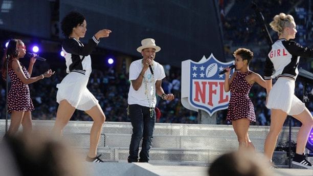Pop singer Pharrell Williams, center, performs at a concert outside CenturyLink Field before an NFL football game between the Seattle Seahawks and the Green Bay Packers, Thursday, Sept. 4, 2014, in Seattle. (AP Photo/Scott Eklund)