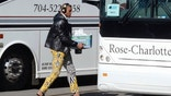 Carolina Panthers quarterback Cam Newton sports zebra-stripe pants as he moves to board a bus on his way to the airport to head to San Francisco for Super Bowl 50 against the Denver Broncos.