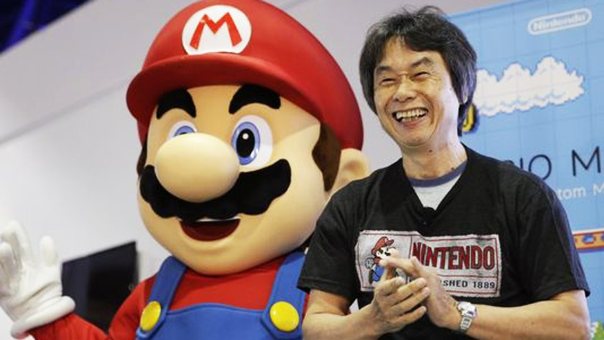 "Shigeru Miyamoto, the creator of ""Mario Bros."" and ""Donkey Kong,"" poses with a Super Mario character at a 2014 promotional event."