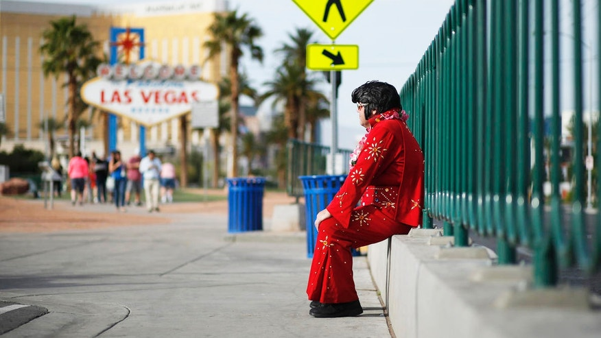 "Ted Payne rests as he works for tips dressed as Elvis at the ""Welcome to Las Vegas"" sign in Las Vegas. For decades, Las Vegas has loved Elvis Presley. But the King's presence in modern day Sin City has lately been diminishing."