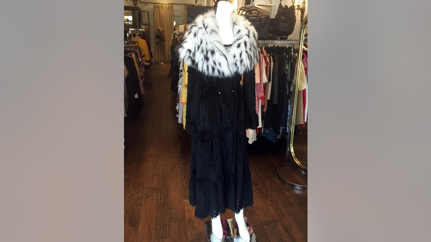 In this Feb. 23, 2016 photo, an Armani dress with a black mink short coat is on display at the Fashionista consignment store in Palm Beach, Fla. The store specializes in high-end women's vintage clothing, shoes, purses and accessories. (AP Photo/Kelly Kennedy)