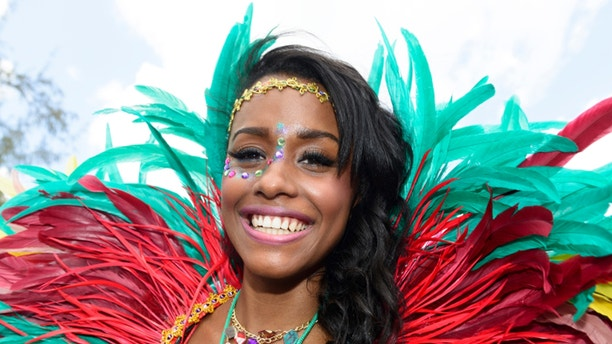 Bridgetown, Barbados - August 5, 2013: Colourful local woman enjoying the Barbados Crop Over festival. This is a traditional harvest festival that had its beginnings on the sugar cane plantations during the islands colonial period.