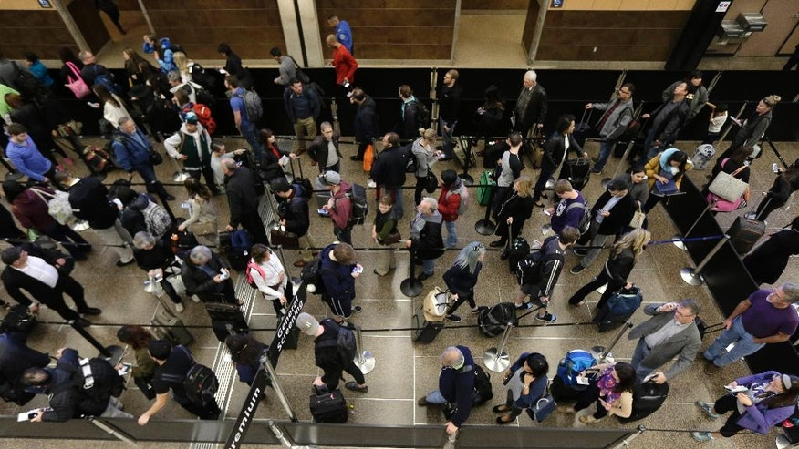 In this March 17, 2016, photo, travelers move through a line for security screening at Seattle-Tacoma International Airport in Seattle. Fliers will likely face massive security lines at airports across the country this summer, with airlines already warning passengers to arrive at least two hours early or risk missing their flight. (AP Photo/Ted S. Warren)
