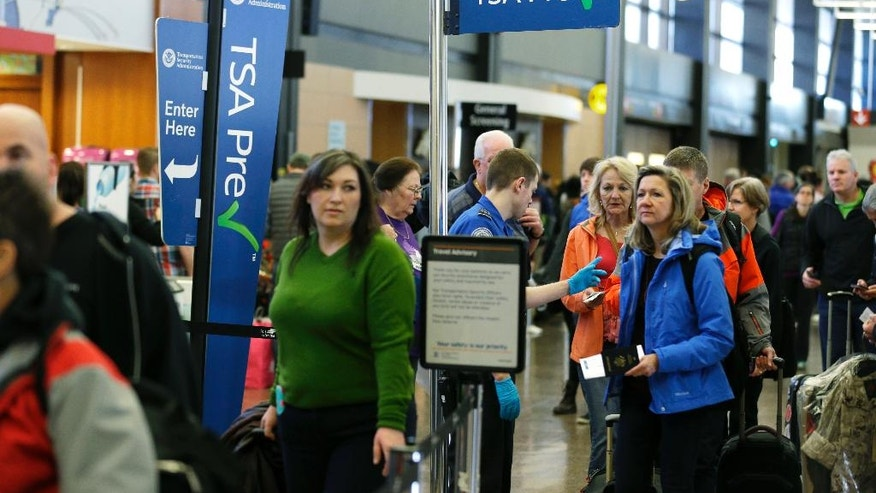 In this March 17, 2016, photo, travelers authorized to use the TSA PreCheck expedited security line at Seattle-Tacoma International Airport in Seattle have their documents checked by Transportation Security Administration workers. Fliers will likely face massive security lines at airports across the country this summer, with airlines already warning passengers to arrive at least two hours early or risk missing their flight. (AP Photo/Ted S. Warren)