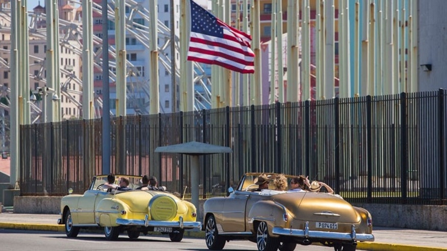 Tourists ride through Havana in vintage American convertibles.