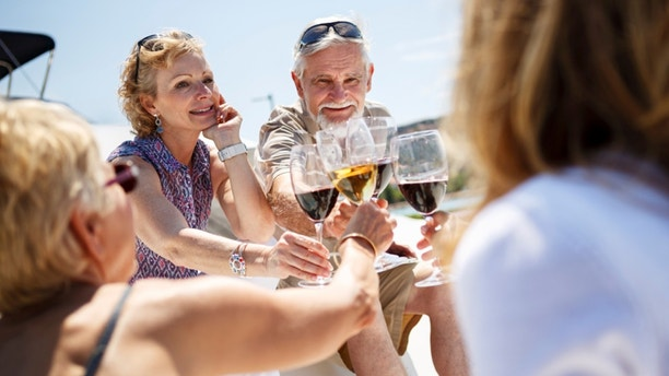 Senior friends toasting each other with wine on yacht