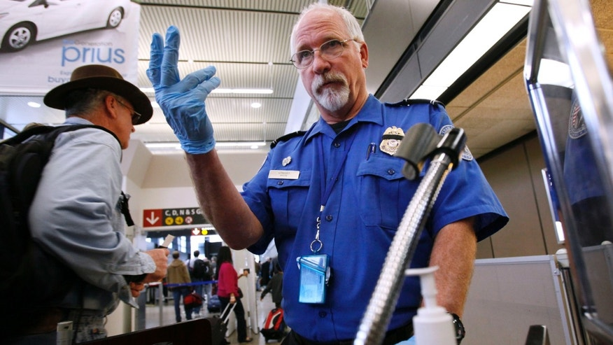 Next? A TSA agent beckons the next passenger at Seattle-Tacoma International Airport.