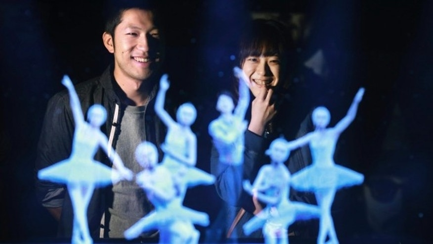 Tomoaki Ishizuka, left, and Yurika Yonekura, right, watch the hologram of Japanese skater Yuzuru Hanyu, center, with ballet dancers with their scanned faces attached at newly opened Hologram Dance Theater at Madame Tussauds in Tokyo, Japan.