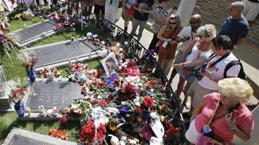 In this Aug. 16, 2012, file photo, Elvis Presley fans visit his grave at Graceland, Presley's Memphis, Tenn., home.