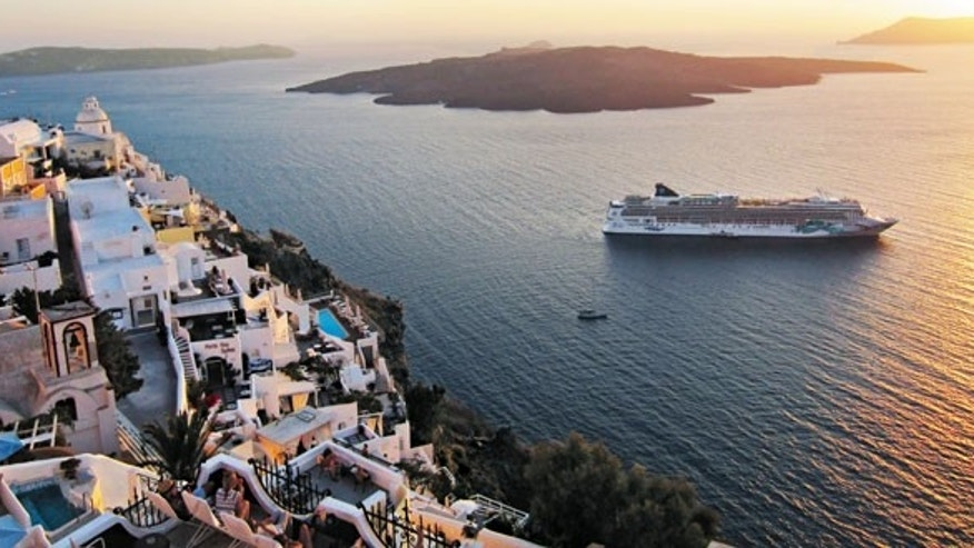 A Norwegian Cruise Line ship sails past Santorini, Greece.