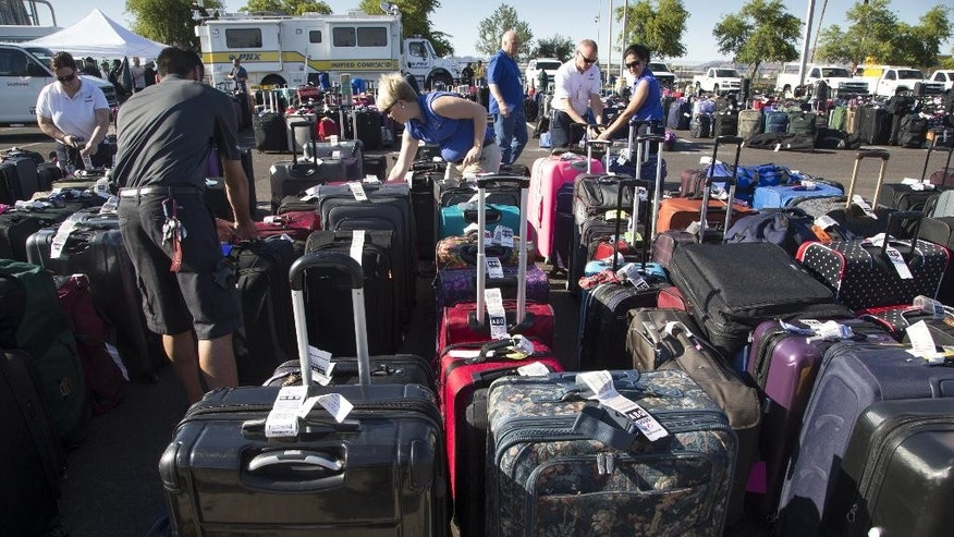 Baggage sits in the special events parking lot, Thursday, May 12, 2016, at Phoenix Sky Harbor International Airport. More than 3,000 checked bags missed their outbound flights in Phoenix  because of a problem with a screening system at Sky Harbor International Airport, officials with Transportation Security Administration said. (Mark Henle/The Republic via AP) MARICOPA COUNTY OUT, NO SALES