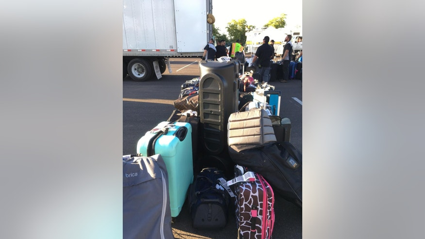 In this Thursday, May 12, 2016 photo workers put passenger luggage on a semi truck at Sky Harbor International Airport in Phoenix. More than 3,000 checked bags missed their outbound flights in Phoenix because of a problem with a screening system at The airport officials with Transportation Security Administration said. (AP Photo/Anna Johnson)