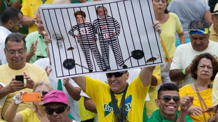 n this March 13, 2016 file photo, a demonstrator holds a poster with the photo of Brazilian president Dilma Rousseff and former President Luiz Inacio Lula da Silva in prison stripes during a protest on Copacabana beach in Rio de Janeiro, Brazil.