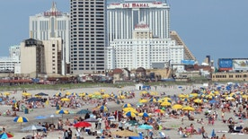 In this photo taken July 3, 2015, people enjoy the beach at Atlantic City, N.J. New Jersey lawmakers are considering a series of far-reaching changes for the seaside resort on Tuesday, Jan. 12, 2016, including asking its casinos to pay more under a tax assistance bill. They also could introduce a bill Tuesday to have the state take over the city's finances.(AP Photo/Wayne Parry) ORG XMIT: RPWP102
