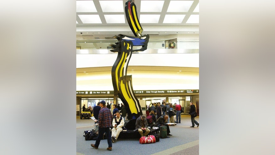 FILE - In this Nov. 22, 2000, file photo, 20th-century pop artist Roy Lichtenstein's sculpture Brushstrokes In Flight serves as a resting spot for Thanksgiving travelers at Port Columbus International Airport in Columbus, Ohio. State lawmakers in Ohio voted Wednesday, May 25, 2016, on a bill that would honor the 94-year-old former astronaut and Democratic U.S. senator by renaming the facility as John Glenn Columbus International Airport. (AP Photo/Jack Kustron, File)