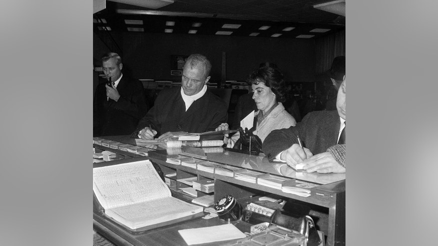 FILE - In this Jan. 21, 1964, file photo, astronaut John Glenn, concluding five days of campaigning in Ohio for his first bid for the Democratic nomination for U.S. Senate, writes out a check for plane tickets as his wife Annie Glenn examines some reading material at Port Columbus airport in Columbus, Ohio. State lawmakers in Ohio voted Wednesday, May 25, 2016, on a bill that would honor the 94-year-old former astronaut and Democratic U.S. senator by renaming the facility as John Glenn Columbus International Airport. (AP Photo/Julian C. Wilson, File)