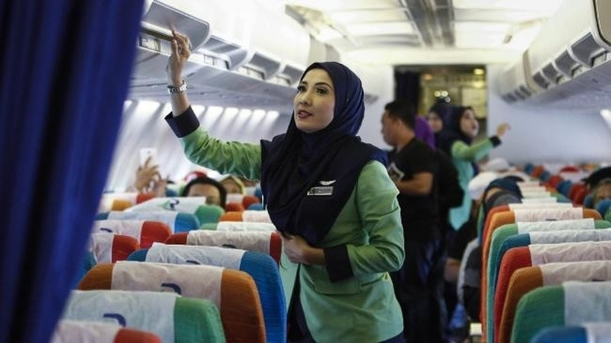 A stewardess for Rayani Air prepares the cabin for takeoff in this Dec. 22, 2015 file photo.