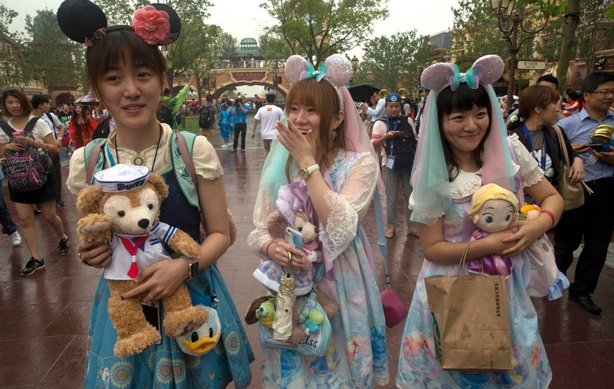 Visitors dress up as they attend the opening day of the Disney Resort in Shanghai, China, Thursday, June 16, 2016. Walt Disney Co. opened its first theme park in mainland China on Thursday at a ceremony that mixed speeches by Communist Party officials, a Chinese children's choir and actors dressed as Sleeping Beauty and other Disney characters. (AP Photo/Ng Han Guan)