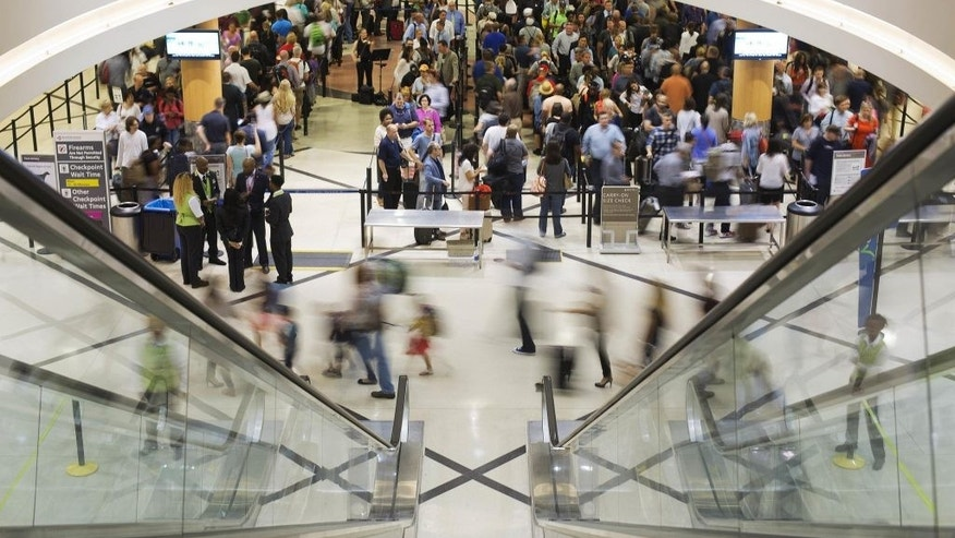 Airline travelers move through a TSA line at Atlanta's Hartsfield-Jackson International Airport.