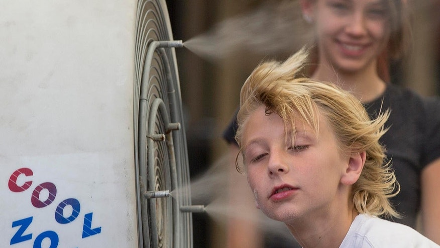 In this 2013 file photo, 10-year-old Easton Martin, of Mesa, Ariz., stops to cool off in a misting fan while walking along The Strip while visiting Las Vegas with his family.