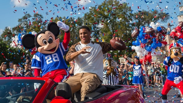 "(Feb. 3, 2014): Super Bowl XLVII MVP Malcolm Smith rides Feb. 3, 2014 with Mickey Mouse in a parade through the Magic Kingdom at Walt Disney World Resort in Lake Buena Vista, Fla. Smith, a linebacker for the Seattle Seahawks, helped lead his team to a 43-8 victory last night over the Denver Broncos in East Rutherford, N.J. After the game, Smith became the NFL's first defensive player to star in the iconic Disney Parks commercial where he proclaimed ""I'm Going to Disney World!"" (Matt Stroshane, photographer)"