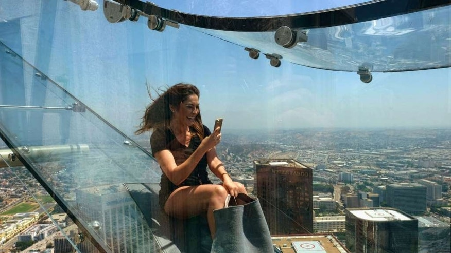 "Angela Cox a reporter with Seven Network Australia takes a photo with her phone as she takes ride down the U.S. Bank Tower building's 1,000 foot tall ""Skyslide"" in downtown Los Angeles on Thursday, June 23, 2016."