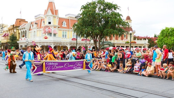 Orlando, USA - August 4, 2013: The start of the A Dream Come True Parade with Disney characters at a very crowded Main Street USA, the entrance to Magic Kingdom amusement park in Walt Disney World and the route of several parades during the day.