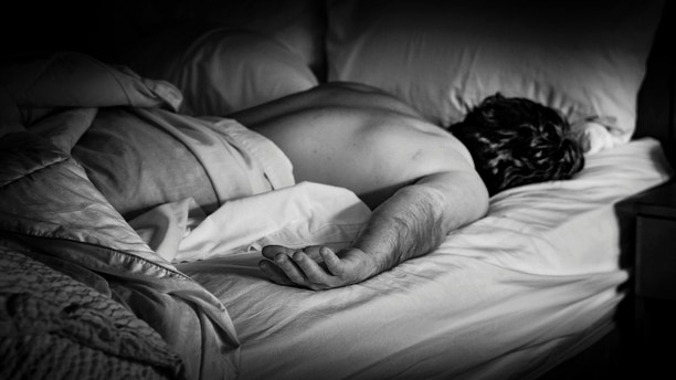 Mature man sleeping in the bed in the hotel room
