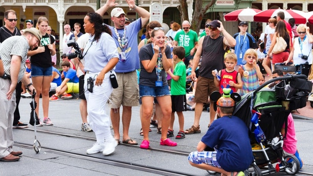 Orlando, USA - August 4, 2013: Parents getting their kids attention for a photo at Main Street USA, the entrance to Magic Kingdom amusement park in Walt Disney World. This is a very popular photo spot as the Cinderella's Caste is in the background.