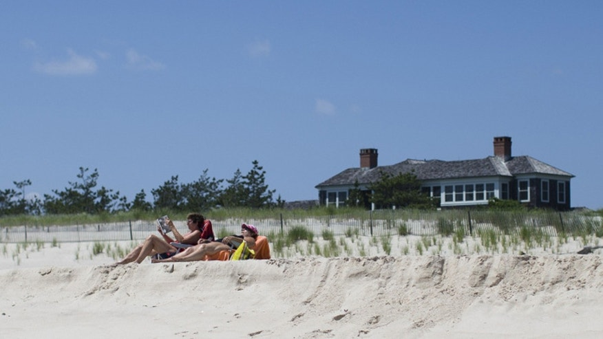 Beachgoers relax near a beachfront property in Southampton, N.Y.