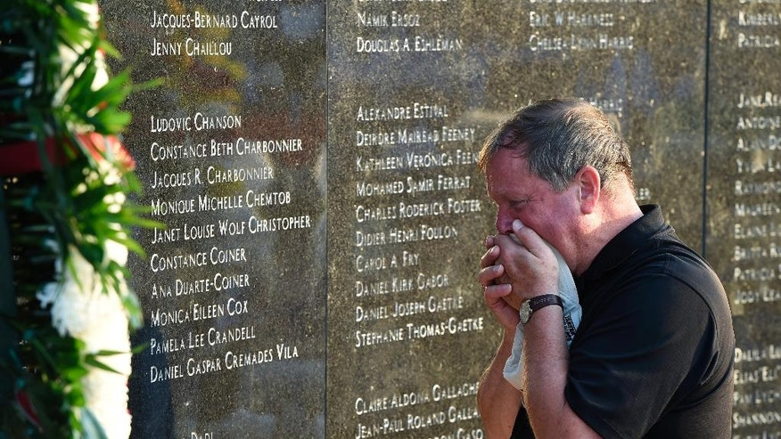 Chris Rhoads, who was the General Manager of Flight Attendants for TWA, reacts at the memorial wall during the 20th anniversary of the TWA Flight 800 plane crash at Smith Point County Park on Sunday, July 17, 2016, in Shirley, N.Y. Families and friends of some of the 230 people killed when a Paris-bound TWA flight 800 jet exploded in the sky off the Long Island coast commemorated the 20th anniversary of the crash that took place on July 17, 1996. (AP Photo/Kathy Kmonicek)