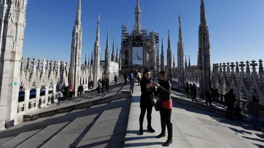 This file photo taken on Sunday, Jan. 25, 2015, tourists relax on the roof atop the Duomo gothic cathedral, in Milan Italy. Italian police say an American tourist spent a night locked on the spectacular rooftop of Milan's Gothic-inspired Duomo cathedral after being overlooked by security.