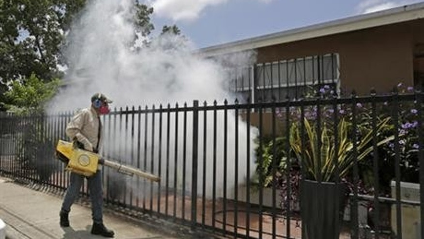 A Miami-Dade County mosquito control worker sprays around a home in the Wynwood area of Miami, Fl. Fifteen cases of the Zika virus have been confirmed in the trendy arts district.