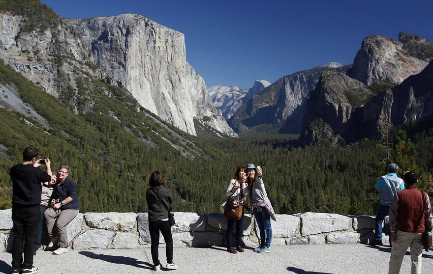 FILE - In this Oct. 17, 2013, file photo, visitors at Tunnel View, like Kaori Nishimura and Eriko Kuboi, from Japan, center facing, enjoy the views of Yosemite National Park, Calif. Tunnel View is a scenic vista which shows off El Capitan, Half Dome and Bridalveil Fall. Yosemite National Park will soon change in an ongoing battle over who owns the intellectual property, park officials said Thursday, Jan. 14, 2016. The move comes in an ongoing dispute with Delaware North, the company that lost a $2 billion bid, the National Park Services largest single contract, to run Yosemite's hotels, restaurants and outdoor activities. (AP Photo/Gary Kazanjian, File)