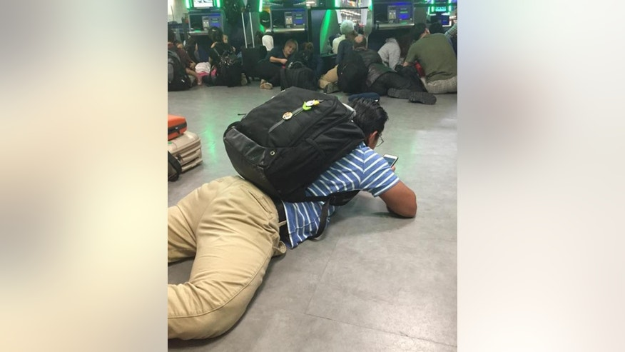 In this Aug. 14, 2016 photo provided by Diana Brooks, arriving passengers in the passport control area of New York's Kennedy Airport stay close to the ground after authorities ordered them to get down on the floor in fear of a possible shooter on the loose. Authorities said that sounds at first suspected to be gunshots, are still under investigation and that no one was hurt. Brooks, a resident of New York, was returning to JFK airport from Copenhagen, Denmark. (Diana Brooks via AP)