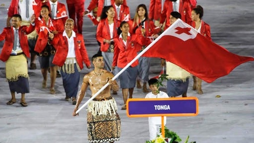 Pita Taufatofua carries the flag of Tonga during the opening ceremony for the 2016 Summer Olympics in Rio de Janeiro, Brazil, Friday, Aug. 5, 2016