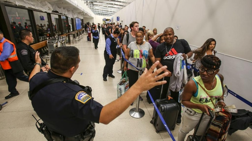 Police officers stand guard as passengers wait in line at Terminal 7 in Los Angeles International Airport, Sunday, Aug. 28, 2016. Reports of a gunman opening fire that turned out to be false caused panicked evacuations at Los Angeles International Airport on Sunday night, while flights to and from the airport saw major delays. Passengers who fled had to be rescreened through security. A search through terminals brought no evidence of a gunman or shots fired, Los Angeles police spokesman Andy Neiman said.  (AP Photo/Ringo H.W. Chiu)