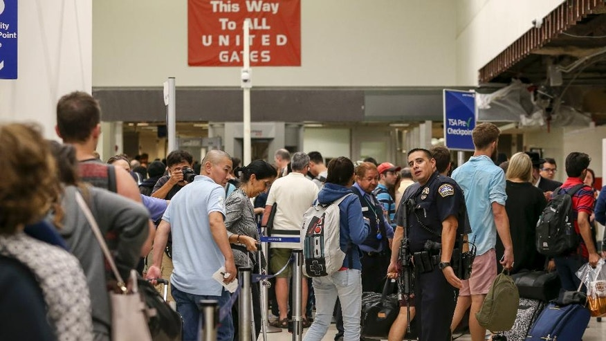 A police officer stands guard as passengers wait in line at Terminal 7 in Los Angeles International Airport, Sunday, Aug. 28, 2016. Reports of a gunman opening fire that turned out to be false caused panicked evacuations at Los Angeles International Airport on Sunday night, while flights to and from the airport saw major delays. Passengers who fled had to be rescreened through security. A search through terminals brought no evidence of a gunman or shots fired, Los Angeles police spokesman Andy Neiman said.   (AP Photo/Ringo H.W. Chiu)