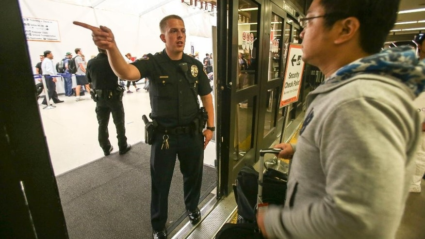 A police officer directs a passenger at Terminal 7 in Los Angeles International Airport, Sunday, Aug. 28, 2016. Reports of a gunman opening fire that turned out to be false caused panicked evacuations at Los Angeles International Airport on Sunday night, while flights to and from the airport saw major delays. Passengers who fled had to be rescreened through security. A search through terminals brought no evidence of a gunman or shots fired, Los Angeles police spokesman Andy Neiman said. (AP Photo/Ringo H.W. Chiu)