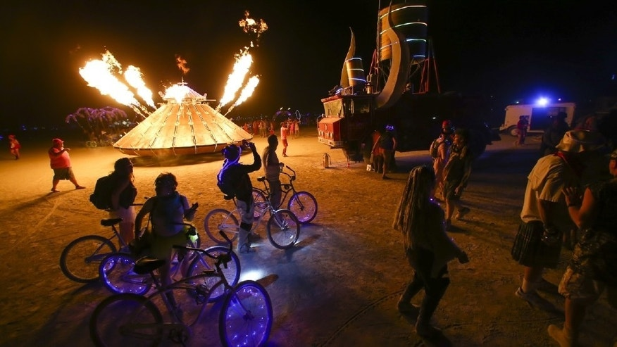 In this Tuesday, Aug. 30, 2016 photo, attendees walk by art cars during Burning Man at the Black Rock Desert near Gerlach, Nev.