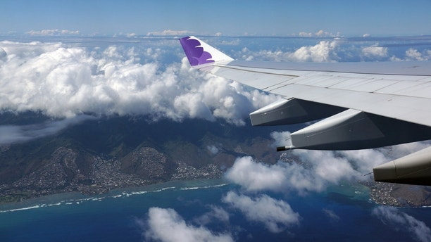 HONOLULU, JUNE 26: Wing of Hawaiian Airlines plane flying in the air above Honolulu, Hawaii and clouds on June 26, 2015.