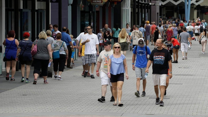 In this Tuesday, Sept. 13, 2016 photo, tourists stroll by the shops and restaurants at the Disney Spring complex in Lake Buena Vista, Fla. Hotel occupancy rates in the Orlando area are down about 2.5 percent for the year through July