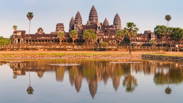 """A panoramic view of the spectacular ruins of the Angkor Wat temple complex in Cambodia.  Taken in golden evening light just before sunset, the scene is reflected in the large lotus pond in front.See several more from Angkor Cambodia, plus Vietnam and Laos:"""