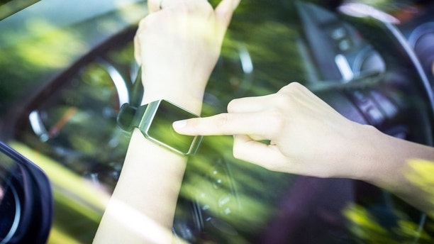 A woman uses smartwatch in the car. Smart watch concept.
