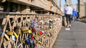 Many padlocks on the brooklyn bridge. They show the love between two people.