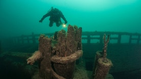 A scuba diver explores an old, wooden shipwreck in Lake Michigan. The waters of the Great Lakes are so cold that they preserve the many wrecks on bottom.
