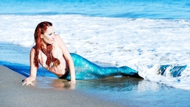 Beautiful red head mermaid, enjoying the sun in the surf