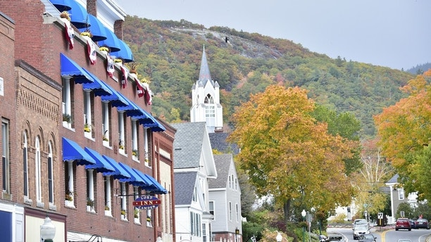 Camden, Maine, USA Bright blue awnings fill the streets of downtown while the steeple of the church is surrounded by Fall Foliage.