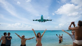 Maho Beach, St. Maarten - November 17, 2015: People at Maho Beach pose for pictures as a KLM Boeing 747 comes in for a landing at Princess Juliana International Airport in St. Maarten.